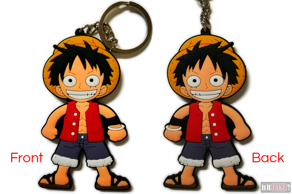 A medium close-up of the fake One Piece Luffy keychain, out of its packaging, shown from the front and back