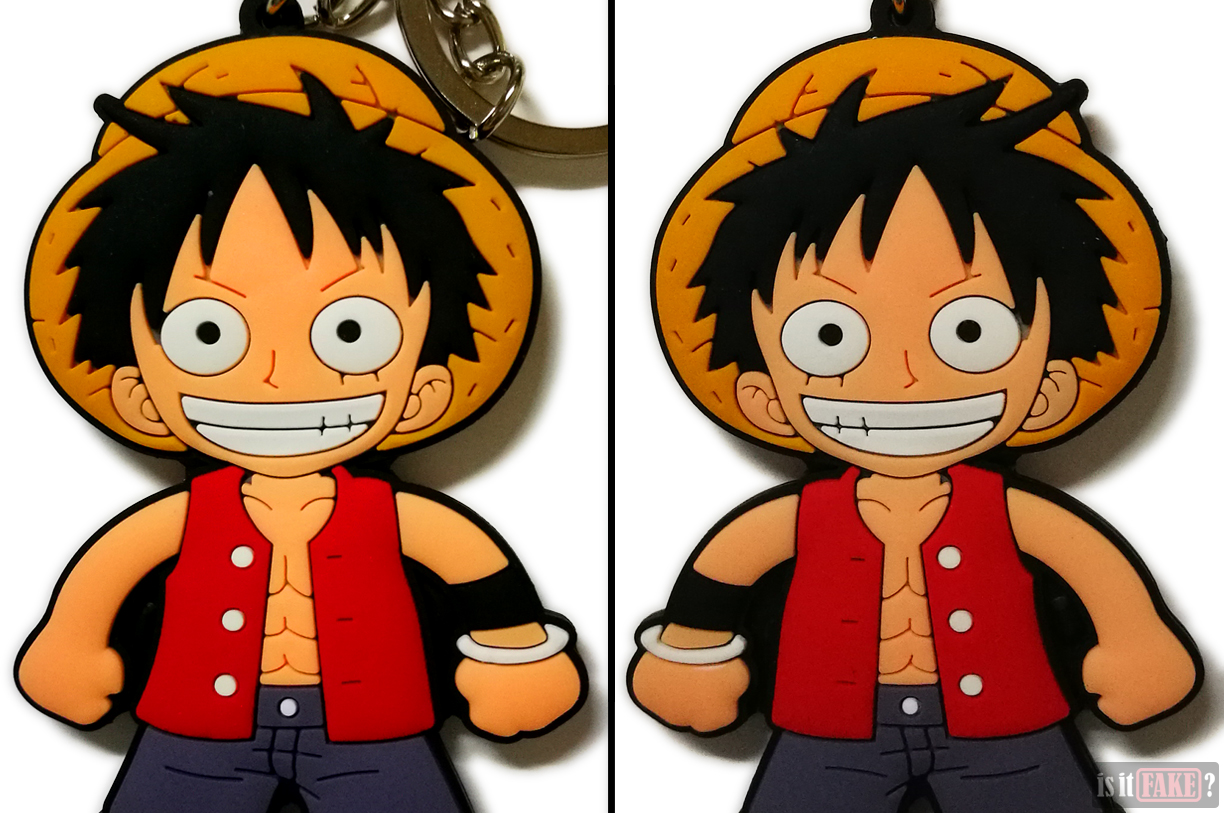 An extreme close-up of the fake One Piece Luffy keychain, out of its packaging, shown from the front and back
