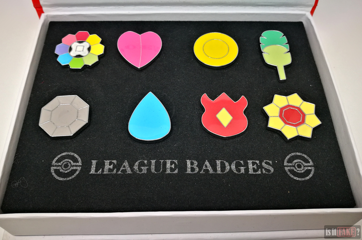 Fake Pokemon badge set box opened to reveal badges fastened to cardboard insert